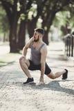 Sportivo che si scalda all'aperto, allungando le gambe Fotografie Stock