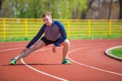 Sportivo che si scalda sulla pista Fotografie Stock