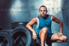 Sportivo che si siede sulla macchina della gomma Concetto di CrossFit, di salute e di forza Immagine Stock Libera da Diritti