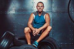 Sportivo che si siede sulla macchina della gomma Concetto di CrossFit, di salute e di forza Fotografie Stock Libere da Diritti