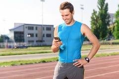 Sportivo che sta con il telefono cellulare sullo stadio immagini stock libere da diritti