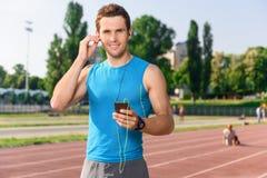 Sportivo che sta con il telefono cellulare sullo stadio fotografia stock