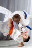Sportivo del tiro di judo di addestramento in judogi e con la cinghia blu Fotografie Stock