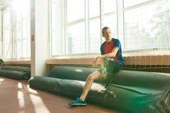 Sportivo dell'amputato che riposa dalla finestra immagine stock