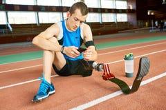 Sportivo dell'amputato che si siede sul pavimento immagine stock libera da diritti