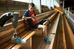 Sportivo disabile che controlla l'inseguitore di attività fotografia stock