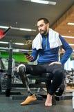 Sportivo disabile che per mezzo del suo smartphone immagini stock
