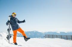 Sportivo felice dello sciatore al fondo panoramico della stazione sciistica di inverno Immagini Stock
