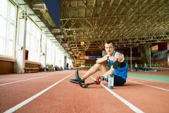 Sportivo handicappato che si siede sulla pista corrente fotografia stock libera da diritti