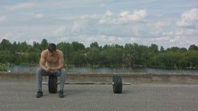 Sportivo maschio che per mezzo del suo telefono cellulare mentre prendendo rottura dopo la formazione intensa attiva all'aperto video d archivio