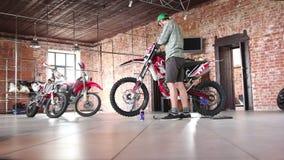 Sportivo maschio che ripara il suo motociclo di enduro video d archivio