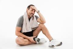Sportivo maturo forte di risata che si siede con l'asciugamano ed acqua fotografia stock libera da diritti