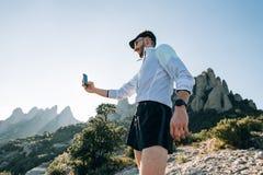 Sportivo o atleta con lo smartphone sulla montagna immagine stock libera da diritti
