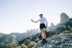Sportivo o atleta con lo smartphone sulla montagna fotografia stock libera da diritti