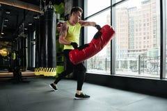 Sportivo serio che fa gli esercizi con il punching ball alla palestra Fotografia Stock