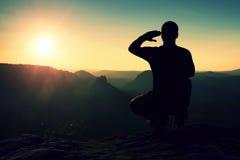 Sportivo solo nel nero La viandante alta nell'occupare la posizione gode della vista al tramonto sul picco di montagna Immagine Stock Libera da Diritti