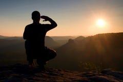 Sportivo solo nel nero La viandante alta nell'occupare la posizione gode della vista al tramonto sul picco di montagna Fotografie Stock Libere da Diritti