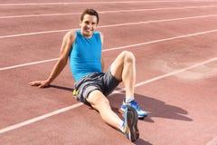 Sportivo sorridente che si siede e che ha resto Immagine Stock Libera da Diritti