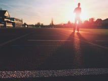 Sportivo sulla pista corrente dello stadio Adulto nell'addestramento di sera Immagini Stock Libere da Diritti