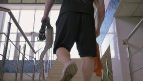 Sportkerl mit Tuch und Gurt klettert Treppe zur Turnhalle für Training und zur Arbeit über Muskeln stock video