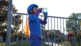 Sportkind trinkt Mineralwasser von der Flasche draußen in der Hintergrundbeleuchtung stock footage
