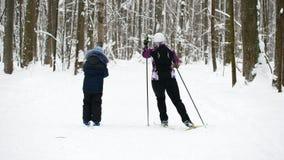 Sportkindheit - Jungenskifahrer, der in Winterschneewald geht stock footage