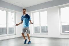 Sportkonditiongenomkörare Hoppande over hopprep för sund man inomhus royaltyfri fotografi