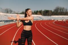 Sportkonditionkvinna som sträcker på stadion Blond flicka för sport som sträcker armar i rinnande arena för sport med många spår royaltyfri bild