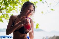 Sportkonditionkvinna som utomhus dricker sund rosa detoxfruktsaft, grönsaksmoothie på strandsommaren Sund kondition Royaltyfri Foto