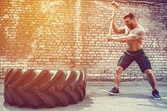 Sportkonditionman som slår hjulgummihjulet med hammarepulkaCrossfit utbildning royaltyfri fotografi