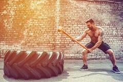Sportkonditionman som slår hjulgummihjulet med hammarepulkaCrossfit utbildning royaltyfria bilder