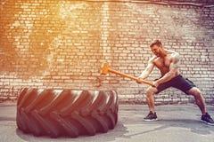 Sportkonditionman som slår hjulgummihjulet med hammarepulkaCrossfit utbildning royaltyfri foto