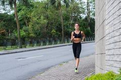 Sportkonditionmodell som joggar på trottoaren i tyst stadsområde Utbildning för kvinnlig idrottsman nen utomhus arkivfoton