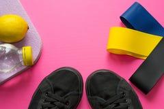 Sportkonzept - bunte Gummibänderexpander nahe schwarzen Turnschuhen, frischer Zitrone, karemat und Flasche mit Wasser auf Rosa lizenzfreies stockbild