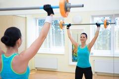 Sportkonzept - junge Frau, die mit Barbell trainiert Lizenzfreies Stockbild