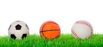 Sportkugeln auf einem grünen Rasen Stockbild