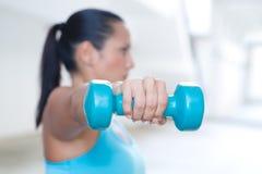 Sportkvinna med den blåa hanteln som gör den utomhus- övningen, endast den dumma klockan och handen i fokus Arkivbild