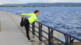 Sportkvinna som övar och sträcker på bakgrund för stadsinvallningberg stock video
