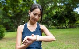 Sportkvinna som använder den smarta klockan i parkera Arkivbild