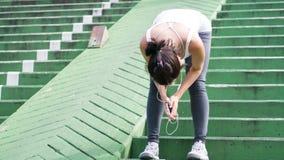 Sportkvinna som använder mobiltelefonspring i stads- byggnad för stad Arkivbild