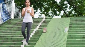 Sportkvinna som använder mobiltelefonspring i stads- byggnad för stad Royaltyfria Foton