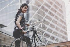 Sportkvinna som b?r hennes cykel upp trappan arkivbild