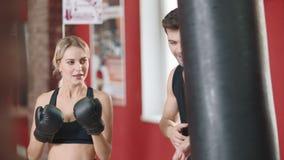 Sportkvinna som boxas den stansa påsen i idrottshallklubba med den personliga instruktören arkivfilmer