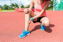 Sportkvinna som får gjord ont på ben royaltyfri bild