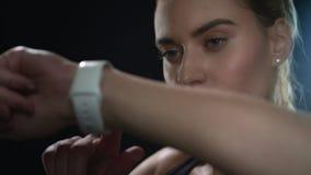 Sportkvinna som f?rest?ende anv?nder den smarta klockan i svart studio St?ende av konditionkvinnan lager videofilmer