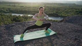 Sportkvinna som gör sträcka utbildning Konditionkvinna som sträcker ben, innan utbildning på det fria på soluppgång eller solnedg arkivfilmer