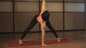 Sportkvinna som gör yoga som sträcker övning stock video