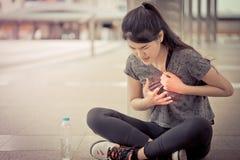 Sportkvinna som har en skada på hennes attac för hjärtabröstkorgsjukdom royaltyfria bilder