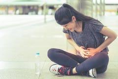 Sportkvinna som har en skada på hennes magknipperoid royaltyfri fotografi