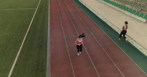 _ sportkvinna som joggar i stadion en ung flicka i sportkläder i utbildning i friidrott arkivfilmer